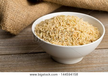 Natural brown uncooked rice in white bowl on wooden table