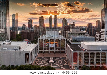 New York NY USA - June 222016: On a summer's evening visitors came to enjoy the sites at Lincoln Center located on the Upper West Side of Manhattan in New York City. View of Metropolitan Opera House with the highrise buildings and sunset in the background
