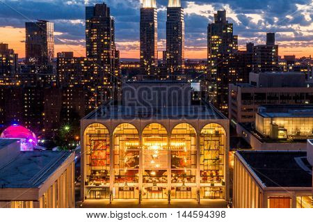 New York NY USA - June 222016: On a summer's evening visitors came to enjoy the sites at Lincoln Center located on the Upper West Side of Manhattan in New York City. Shown is the Metropolitan Opera House with the highrise buildings and sunset in the backg