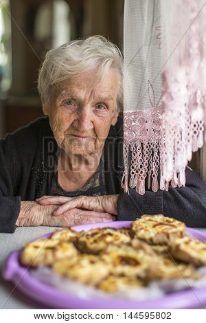 An elderly woman sitting at a table with a Karelian pasty.