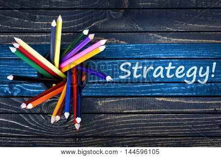 Strategy text painted and group of pencils on wooden table