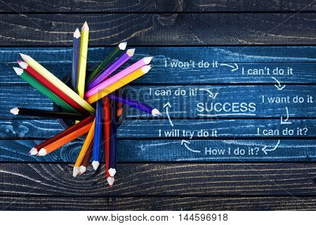 Success text painted and group of pencils on wooden table