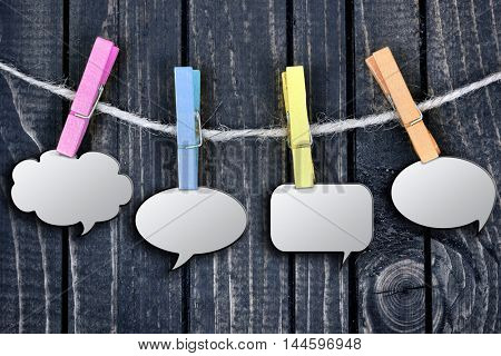 Chat bubbles hanging on clips and wooden wall