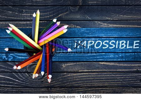Impossible text painted and group of pencils on wooden table