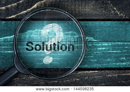 Solution text painted and magnifying glass on wooden table
