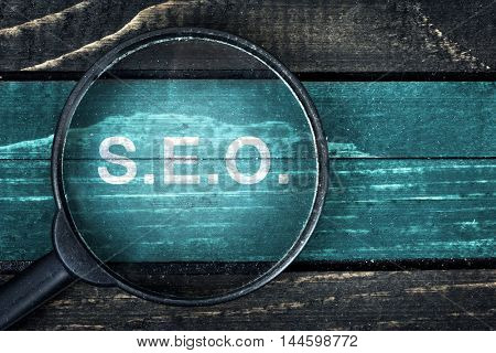 SEO text painted and magnifying glass on wooden table