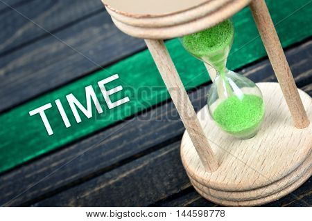Time text and hourglass on wooden table