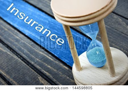 Insurance text and hourglass on wooden table