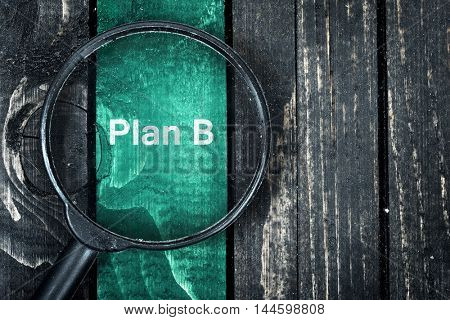 Plan B text painted and magnifying glass on wooden table