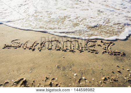 Word Summer handwritten on sandy beach with soft ocean wave on background