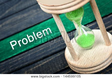 Problem text and hourglass on wooden table