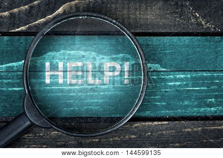 Help text painted and magnifying glass on wooden table