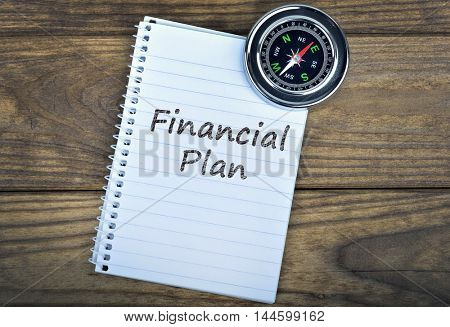 Financial Plan text and metallic compass on wooden table