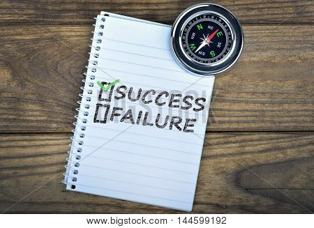 Success text and metallic compass on wooden table