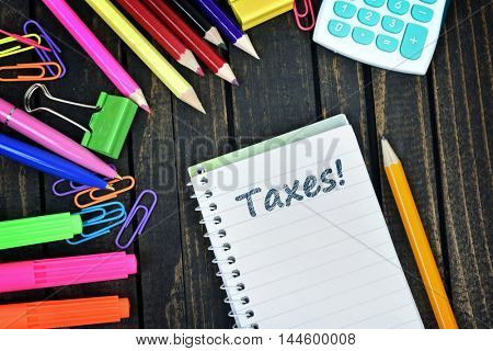 Taxes text on notepad and office tools on wooden table