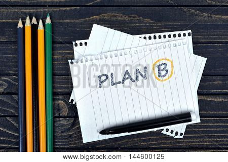 Plan B text on notepad and office tools on wooden table
