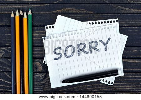 Sorry text on notepad and office tools on wooden table