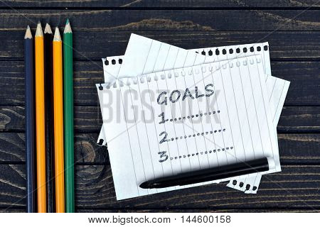Goals list on notepad and office tools on wooden table