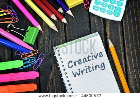 Creative writing text on notepad and office tools on wooden table