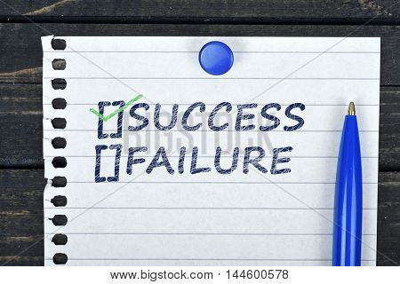 Success text on page and pen on wooden table