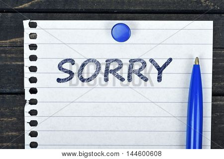 Sorry text on page and pen on wooden table