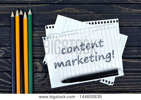 Content marketing text on notepad and office tools on wooden table