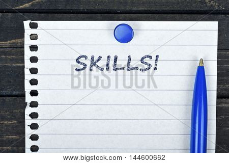 Skills text on page and pen on wooden table