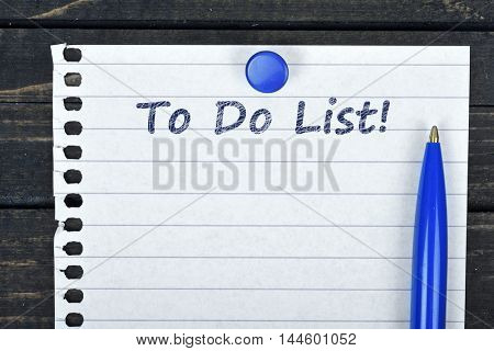 To do list text on page and pen on wooden table
