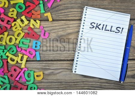 Skills text on notepad and magnetic letters on wooden table