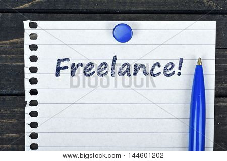 Freelance text on page and pen on wooden table