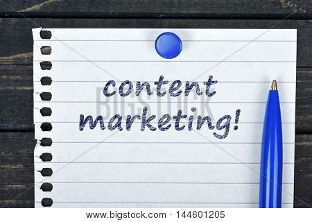 Content Marketing text on page and pen on wooden table