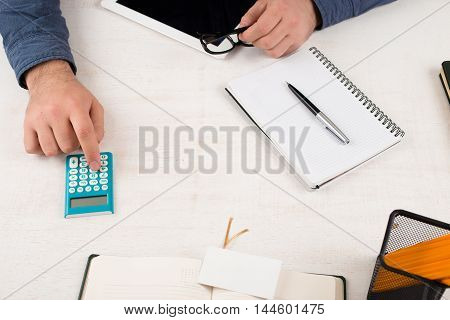 Businessman calculate on the calculator in home office on white table. Home desktop background