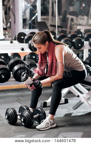 Having rest to drink athletic woman at gym. Young sporty female athlete with bottle of water in hands and towel on her neck sitting near dumbbells.
