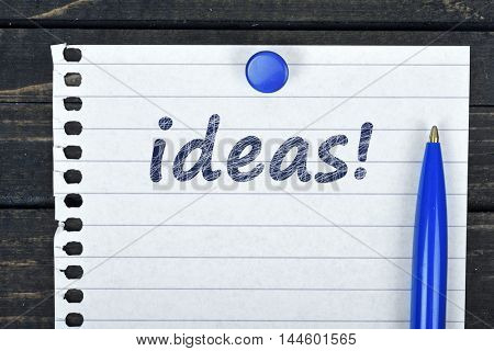 Ideas text on page and pen on wooden table