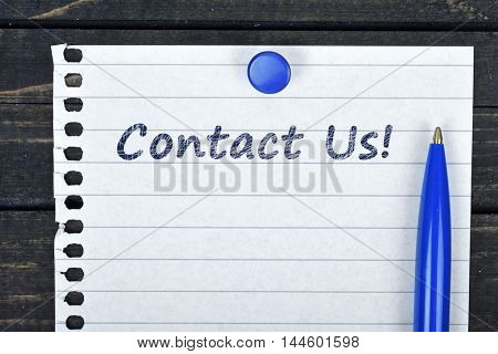 Contact Us text on page and pen on wooden table