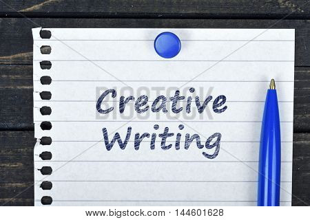 Creative Writing text on page and pen on wooden table