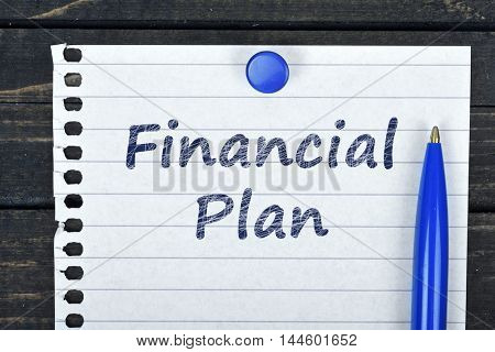 Financial Plan text on page and pen on wooden table