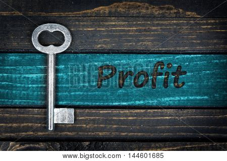 Profit word and old key on wooden table