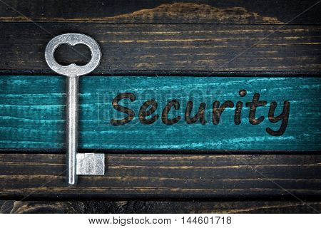 Security word and old key on wooden table