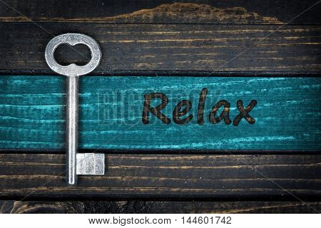 Relax  word and old key on wooden table
