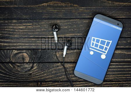 Shopping Cart on phone screen and earphones on wooden table