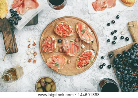 Bruschetta sandwich with Italian ham on wooden board on white table with grapes olives and red wine top view. Different appetizers for wine with red wine on white table