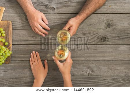 Couple clinking glasses with white wine sitting behind wooden table top view