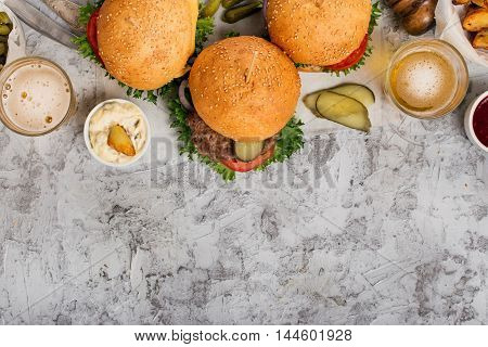 Three fresh homemade different burgers and lager on light gray surface with copy space top view