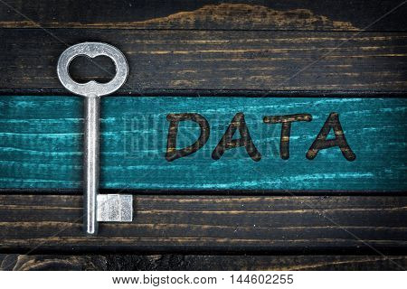 Data word and old key on wooden table