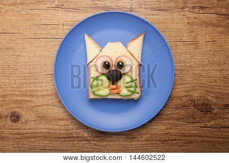 Funny cat made of toast cheese and vegetables on plate and desk