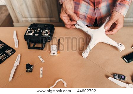Disassembled drone on table. Unrecognizable person near table with elements for quadrocopter building. Modern technologies, innovation, hobby, aeromodelling concept