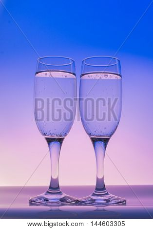 Two champagne glass with bubbles on blue and yellow background