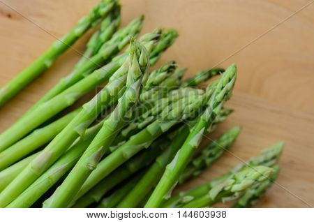 fresh green asparagus on wooden chopping board