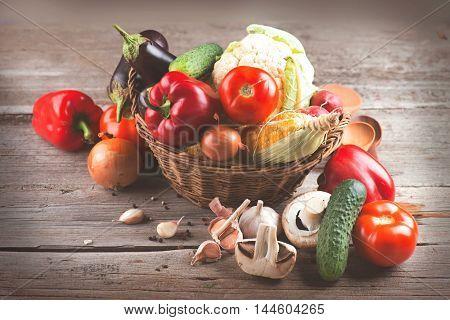Healthy Organic Vegetables in basket on Wooden Background. Vegan food over wood. Vegetarian diet